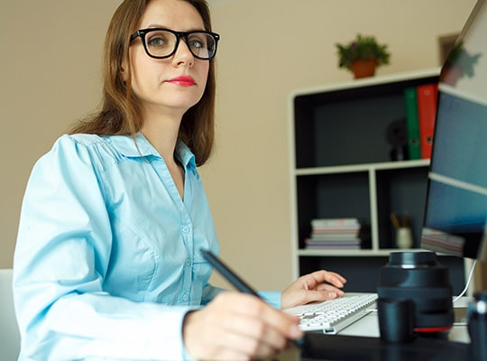Frau mit Brille sitzt am Schreibtisch und zeichnet etwas auf einem Grafiktablett